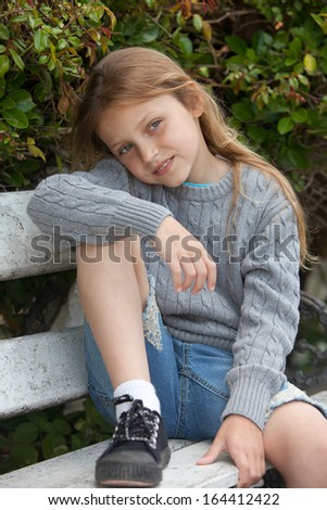 smiling little girl sitting on the bench