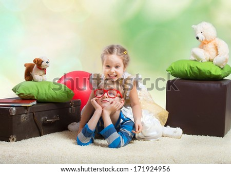 Smiling little girl sitting on the brother's back - stock photo
