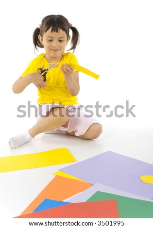 Smiling, little girl sitting on the floor. Cutting paper with scissors. White background - stock photo