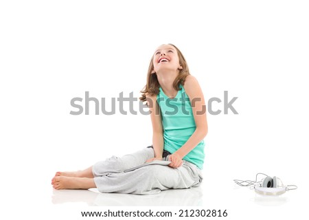 Smiling little girl sitting on the floor with digital tablet and headphones and looking up. Full length studio shot isolated on white. - stock photo