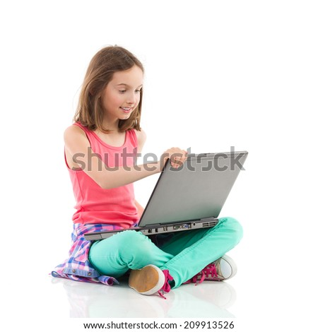 Smiling little girl sitting on the floor with legs crossed and using the laptop. Full length studio shot isolated on white.