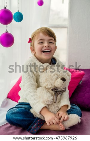 Smiling little girl sitting on windowsill and embraces a teddy bear. New Year's box decorated with colored balls