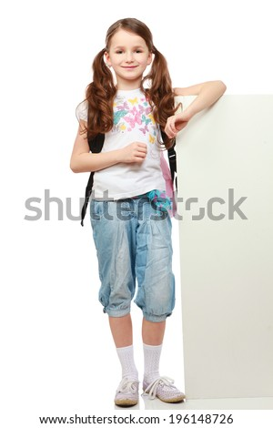 Smiling little girl standing near empty white board - stock photo