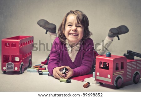 Smiling little girl surrounded by toys - stock photo