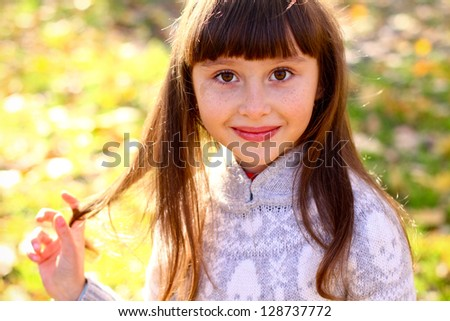 Smiling little girl walking in the autumn park and touches her hair