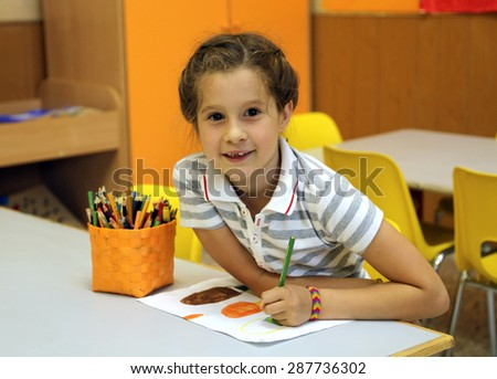 smiling little girl while drawing with the pencil colours at school - stock photo