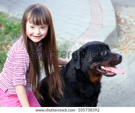 Smiling little girl with a big black dog - stock photo