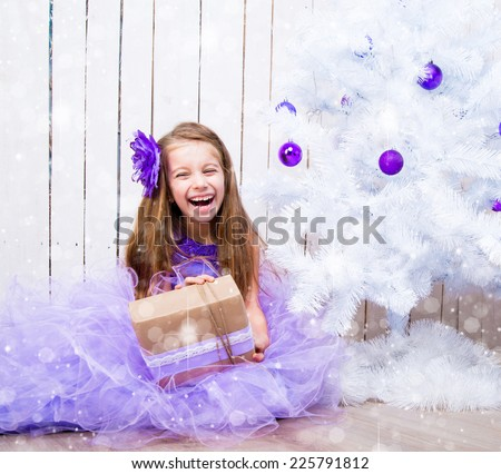 smiling little girl with a gift in hands near white Christmas tree - stock photo
