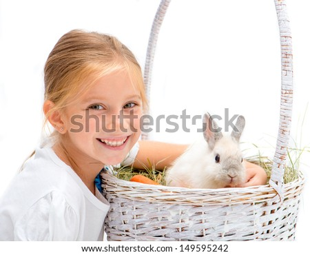 Smiling Little girl with a rabbit in a basket - stock photo