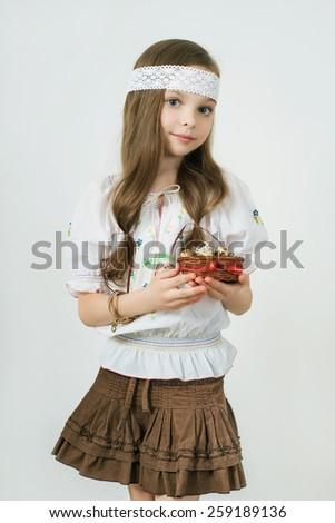 Smiling little girl with basket full of colorful easter eggs and flowers. Easter. Spring. - stock photo