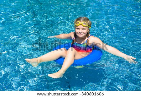 Smiling little girl  with blue life ring has fun in the swimming pool - stock photo