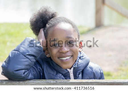 Smiling little girl with hand on head - stock photo