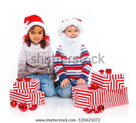 Smiling little mullato girl and her brother in Santa's hat with gift box, isolated on white - stock photo