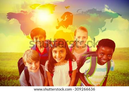 Smiling little school kids in school corridor against green field under blue sky - stock photo