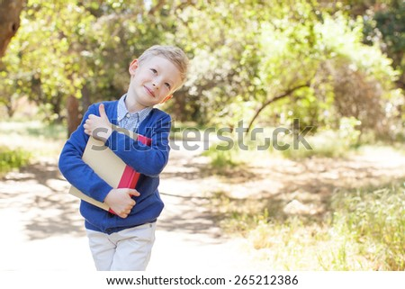 smiling little schoolboy holding book ready to go to school, back to school concept - stock photo