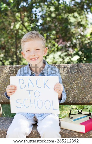 smiling little schoolboy ready to go to school, back to school concept - stock photo