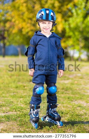 Smiling little skater boy in blue sportswear posing outdoors - stock photo