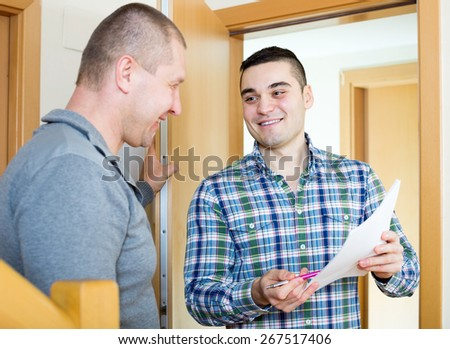 Smiling lodger talking neighbor with papers at doorway. Focus on the right man - stock photo