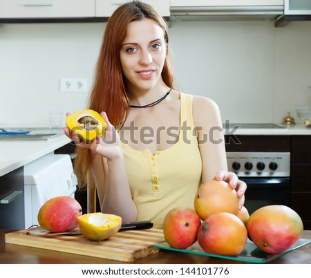Smiling long-haired woman eating mango at home kitchen