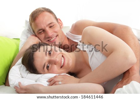 Smiling loving couple lying in bed with their arms around each other smiling happily at the camera after a refreshing nights sleep