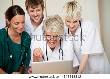 Smiling male and female doctors looking at laptop in hospital - stock photo