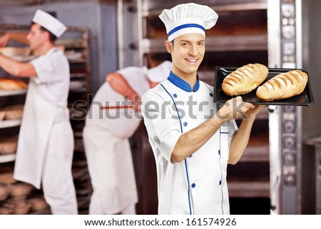 Smiling male baker posing with freshly baked breads in bakery while others working