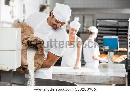 Smiling male baker pouring flour in kneading machine at bakery - stock photo