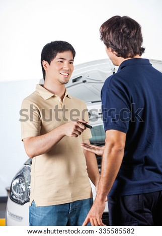 Smiling male client giving car keys to mechanic in auto repair shop