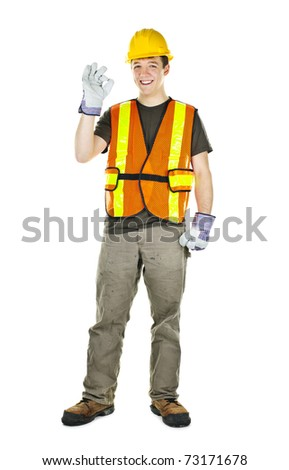 Smiling male construction worker showing okay sign standing isolated on white background