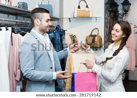 Smiling male customer with cheerful female shop assistant at boutique. Focus on man - stock photo
