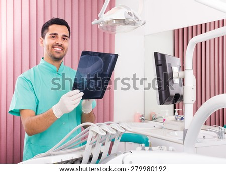 Smiling male dentist looking x-ray scan