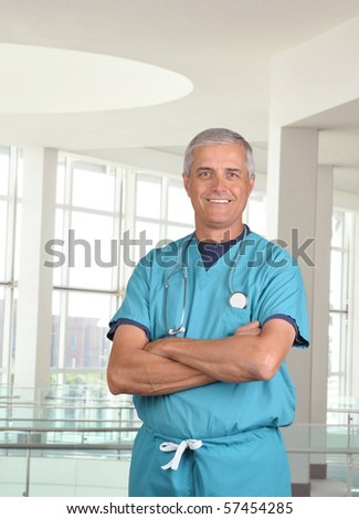 Smiling male doctor in scrubs with a stethoscope around his neck and his arms crossed. Vertical format 3/4 torso view in modern looking medical facility. - stock photo