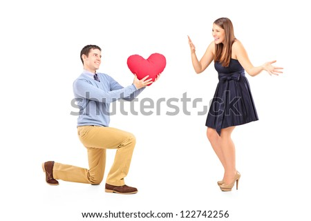 Smiling male kneeling with red heart and surprised woman isolated on white background - stock photo
