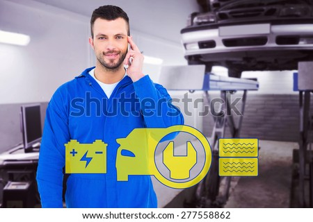 Smiling male mechanic using his mobile phone against auto repair shop - stock photo