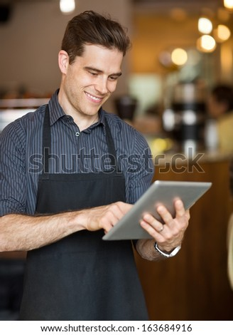 Smiling male owner surfing internet on digital tablet in cafeteria - stock photo