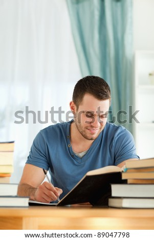 Smiling male student reviewing his subject material