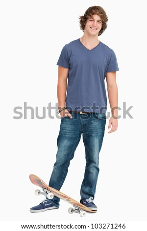 Smiling male student with a skateboard against white background - stock photo