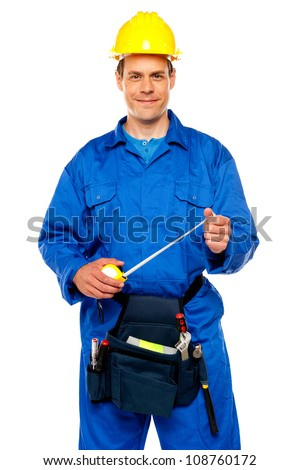 Smiling male worker wearing yellow safety hat holding measuring tape - stock photo