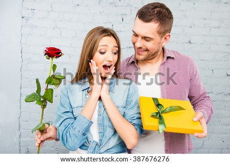 Smiling man and happy surprised woman with rose and gift - stock photo