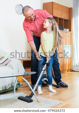 Smiling man and his cute little daughter hoovering in the living room together