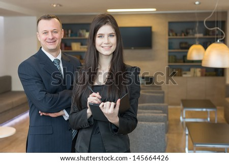 Smiling man and woman in business suits standing in office room, focus on a woman.