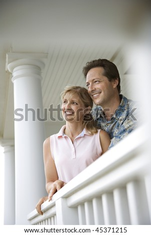 Smiling man and woman look out from a house porch, lean on a railing. Vertical shot. - stock photo