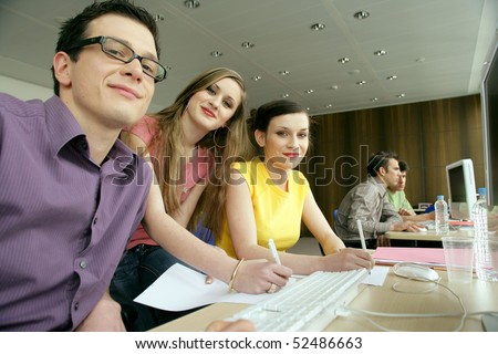Smiling man and women in front of a laptop computer - stock photo