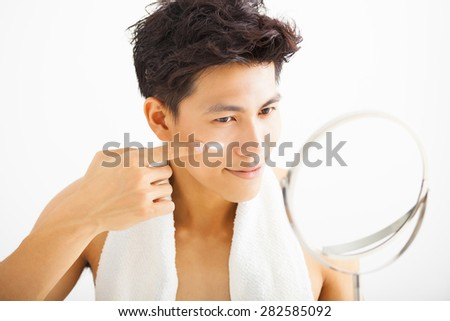 smiling man applying cream lotion on face - stock photo