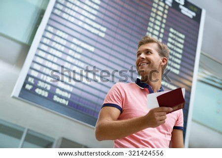 Smiling man at board at the airport - stock photo