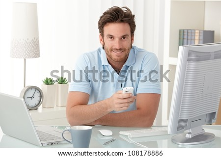 Smiling man at desk with mobile phone handheld, looking at camera, having computer. - stock photo