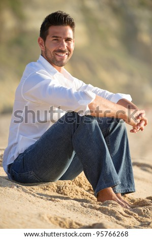 smiling man at the beach seated on the sand - stock photo