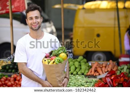 Smiling man carrying a shopping paper bag full of organic fruits and vegetables at an open street market. - stock photo