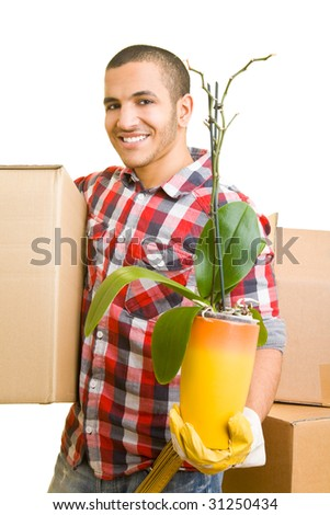 Smiling man carrying boxes and a plant - stock photo