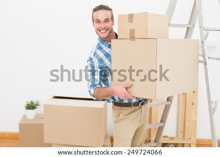 Smiling man carrying cardboard moving boxes at home in the living room - stock photo